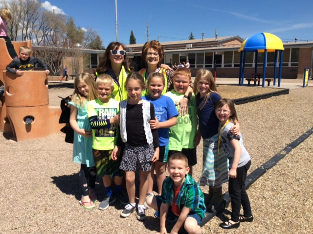 Picture of the principal, a paraeducator and students on playground