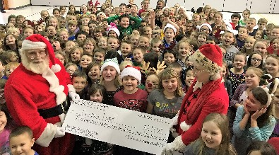 Santa, his helper, and Pinecreek students pose with a check for the Arianna Fund.