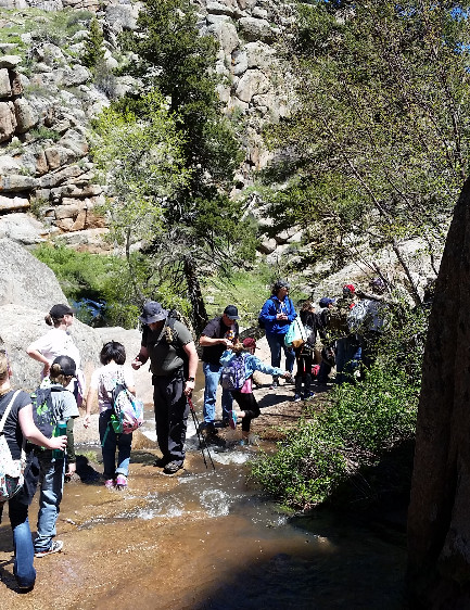 image of students and adults walking through stream along hiking trail.
