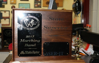 "This is a picture of the plaque that State Marching Band brought home.  The caption says, ""Congratulations Marching Band for bringing home a Superior."""