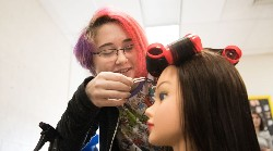 Student fixing hair in cosmetology class