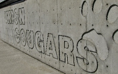 Union Cougars logo carved into the stone wall of the softball dugout