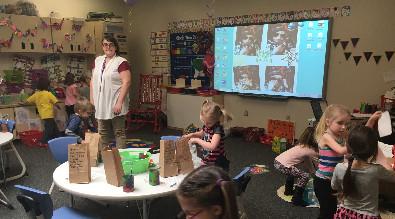 Pre-k students putting non-perishables in bags.