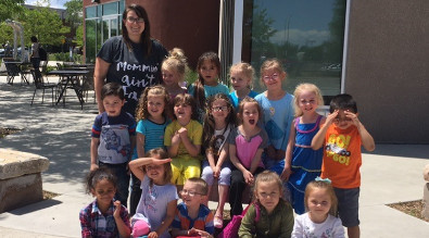 Pre K teacher with her class in front of a building