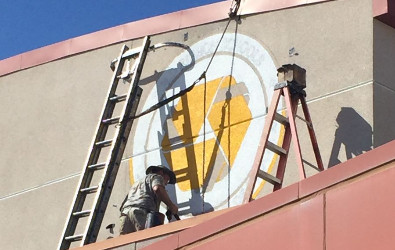 Workers setting up the Gold Ribbon Award logo on the side of the school building.