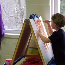 Young student painting in classroom