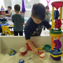 Pre-K student learning through play at a classroom sandbox