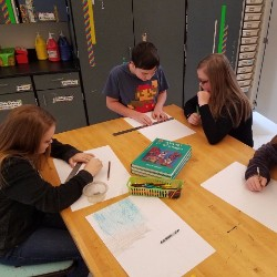 Students gathered around a table collaborating for learning