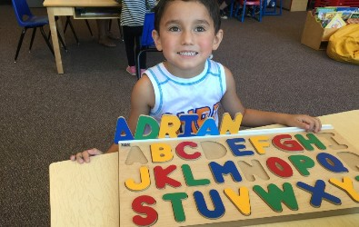 a preschool student playing an ABC puzzle