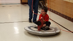 Students on a hoverboard in the school.
