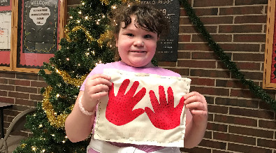 Photo of a student with artwork of two red hands.