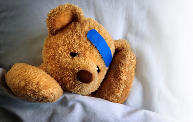Photo of a teddy bear with a bandage from an injury.
